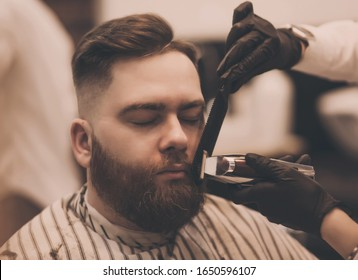 Grooming of real man. Bearded man getting beard haircut at hairdresser while sitting in chair at barbershop