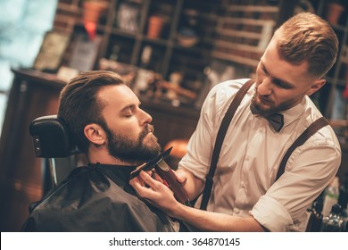 Grooming of real man. Side view of young bearded man getting beard haircut at hairdresser while sitting in chair at barbershop