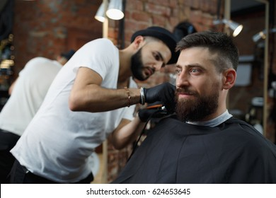 Grooming  for real man. Young bearded man getting haircut by hairdresser with electric razor while sitting in chair at barbershop