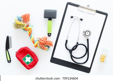 grooming set with pets cure tools and stethoscope on white background top view