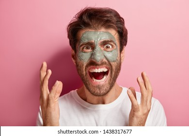 Grooming and skin care concept. Annoyed young man applies nourishing clay mask on face, gestures angrily, irritated with wrinkles under eyes, wants to look young and refreshed, isolated on pink wall