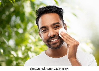 grooming, skin care and people concept - smiling young indian man cleaning his face with cotton pad over green natural background
