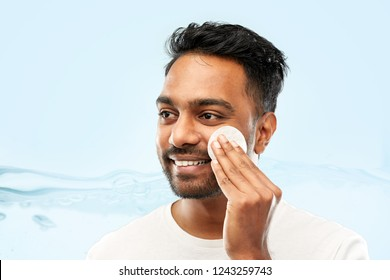 grooming, skin care and people concept - smiling young indian man cleaning his face with cotton pad over blue background with bubbles in water splash