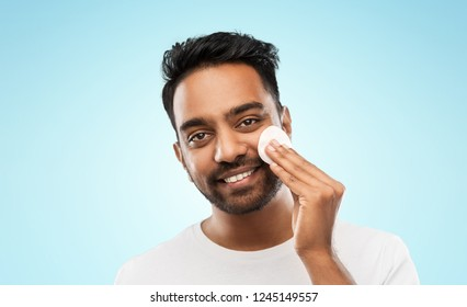 grooming, skin care and people concept - smiling young indian man cleaning his face with cotton pad over blue background