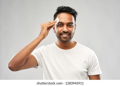 grooming, skin care and people concept - smiling young indian man cleaning his face with cotton pad over grey background