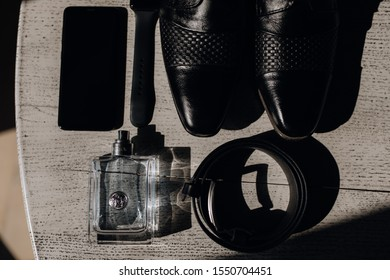 Groom's accessories like as shoes,  belt,  perfumes, and telephone lie on the wooden surface