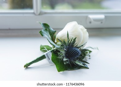 A groom's buttonhole with a single white rose