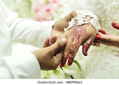 groom's hand putting a wedding ring on the bride's finger