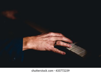 Groom's hand with ring on the piano
