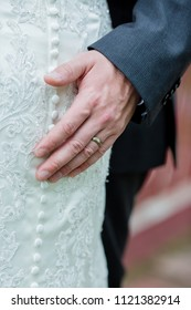 Groom's hand touches bride gently on wedding day wearing wedding band. Outdoor ceremony.