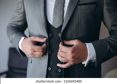 Grooms morning preparation, handsome groom getting dressed and preparing for the wedding, in dark blue suit.