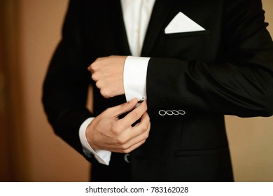 Grooms morning preparation, handsome groom getting dressed and preparing for the wedding, fixes cufflinks