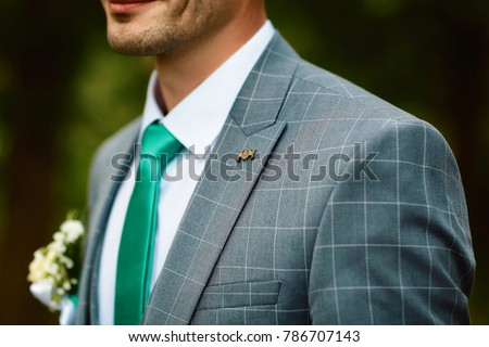 Grooms morning preparation, handsome groom getting dressed and preparing for the wedding, in gray suit in a cell with a brooch