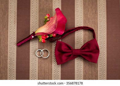 Groom's morning. Wedding accessories in red colors. Tie-butterfly, rings, boutonniere