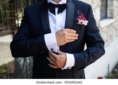 groom's wedding preparation straightens cufflinks - Shutterstock ID 1916501642