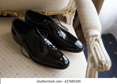 Groom's wedding shoes on top of white chair,  Man's black lace up leather shoes, Wedding day attire