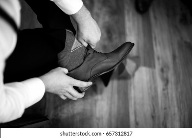 Groomsman getting ready and putting his shoes on