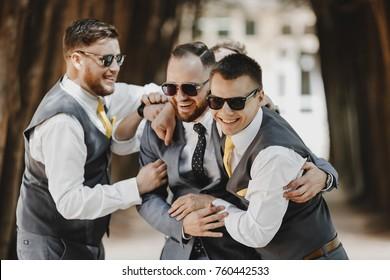 Groomsmen in black sunglasses hug groom tightly posing in the park