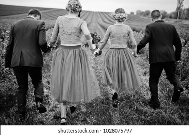 Groomsmen and bridesmaids running in blackcurrant field on a wedding day. Black and white photo.