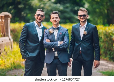 Groomsmen and groom posing outdoors on the wedding day. Funny wedding moment for best groom friends. Mens hug each other.