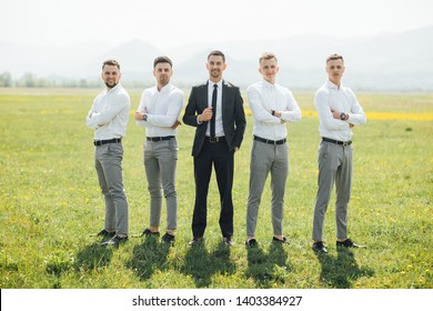 Groomsmen and groom posing outdoors on the wedding day. Funny wedding moment for best groom friends. Man hug each other. -
