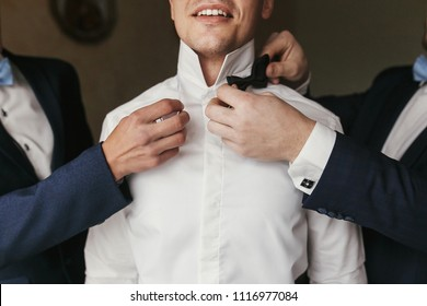 Groomsmen helping groom getting ready in the morning in the room. man hands putting on jacket and bow tie, standing at window light in hotel. preparation for wedding day