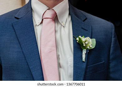 Groomsmen pink tie. Babies breath boutonniere on a royal blue suit jacket. A groomsmen's closeup of his tie and formal wear in Baton Rouge, Louisiana.