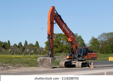 GROOTEBROEK , THE NETHERLANDS – May 3 , 2018 : Parked orange crane with caterpillar tracks for groundwork
