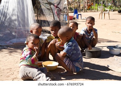 GROOTFONTEIN, NAMIBIA - MAY 16: san bushman children eating on the ground in their  village in  kalahari desert in Namibia  may 16, 2017 in Grootfontein, Namibia