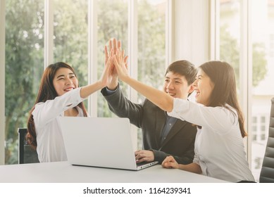Gropu of young Asian business people giving high five to celebrate success on working project in meeting room