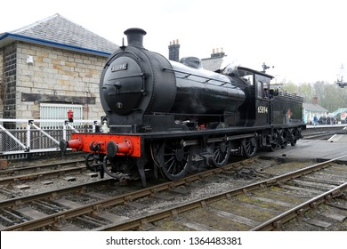 GROSMONT, NORTH YORKSHIRE, UK : 7 APRIL 2019 : Preserved British Steam Engine 65894, which was built in 1923 at Darlington, is leaving a Grosmont Station on the North Yorkshire Moors Railway