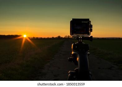 Gross Gerau, Germany - November 06 2020: Modern action camera shooting a beautiful sunset near Gross Gerau, Germany.
