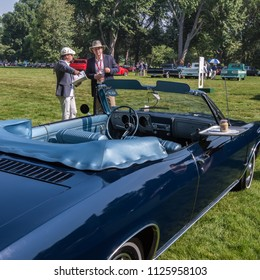 GROSSE POINTE SHORES, MI/USA - JUNE 17, 2018: Judges review a Chevrolet Corvair car at the EyesOn Design car show, held at the Edsel and Eleanor Ford House, near Detroit, Michigan.