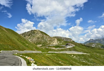 The Grossglockner High Alpine Road (in German Großglockner-Hochalpenstraße)  is the highest surfaced mountain pass road in Austria. Summer with  blue skyes green mountains and street for wallpaper.