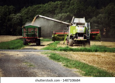 Grossropperhausen, Germany - August 12. 2019: Modern class Lexion 570, refilling the harvest in the area near the village of Grossropperhausen on August 12. 2019.