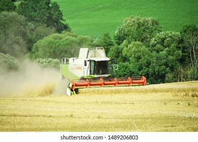 Grossropperhausen, Germany - August 12. 2019: Modern class Lexion 570, refilling the harvest in the area near the village of Grossropperhausen on August 12, 2019.