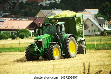 Grossropperhausen, Germany - July 7, 2019: Krone TX 460D harvest wagon with John Deere 6230R tractor harvesting near Grossropperhausen village on July 7, 2019.