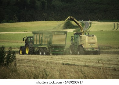Grossropperhausen, Germany - July 7, 2019: Krone X Disc 620 shredder and John Deere 6230R with crown TX 460D at the barley harvest near the village of Grossropperhausen on July 7, 2019.