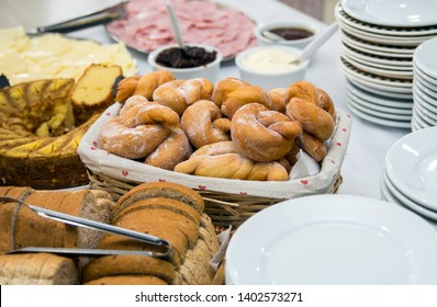 Grostoli, bread and cake placed inside baskets, in typical Italian meal with colonial food.