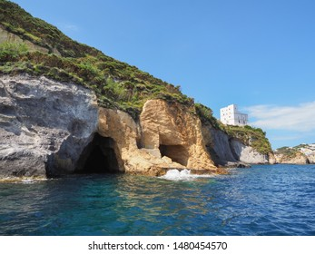 Grotte di Pilato caves and white house on a steep rock. Beautiful landscape. Ponza. Pontine Islands. Italy. Travel around the island. Boat trip. Multicolored mountains. View of the Tyrrhenian Sea.