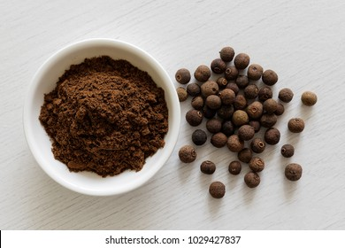 Ground allspice in white ceramic bowl isolated on white wood background from above. Whole allspice.