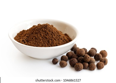 Ground allspice in white ceramic bowl isolated on white. Whole allspice.