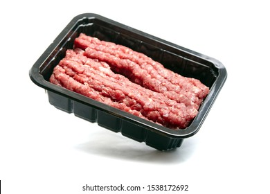 Ground beef in a black plastic tray isolated on white background. Uncooked mincemeat. Forcemeat, fresh raw minced meat