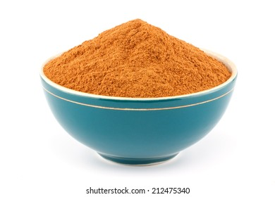 Ground cinnamon powder in green porcelain bowl on white isolated background