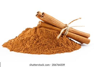 Ground cinnamon powder and sticks on white isolated background