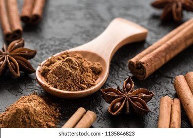 ground cinnamon spice powder in wooden spoon, on dark concrete background.  Cinnamon, whole sticks  with a heap of powder.  Ingredients for cooking. Banners of herbs and spices. Space for text