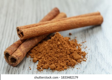 Ground cinnamon and cinnamon sticks on a wooden base