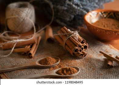 Ground cinnamon, cinnamon sticks, tied with jute rope on old straw bag background in rustic style