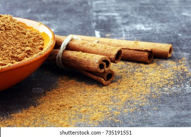 Ground cinnamon, cinnamon sticks, tied with jute rope and cinnamon powder in rustic style.