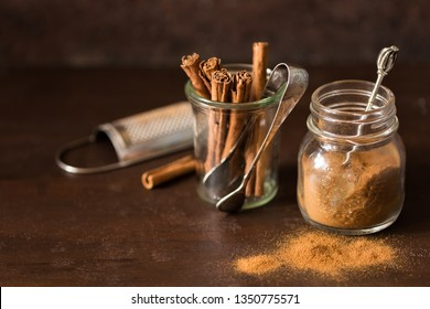 Ground cinnamon and cinnamon sticks with tongs and grater on brown background.